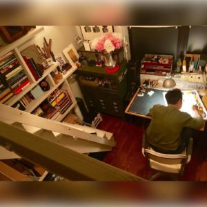 View from upstairs: Aliza working on a painting at her drafting table.