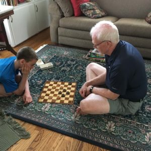 Hilary's dad and nephew sharing a game of checkers together