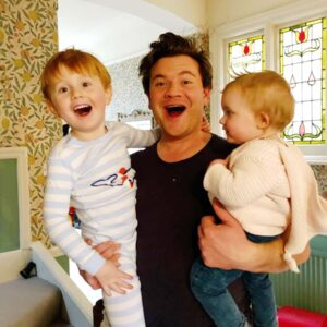 Sebastian in London, England, visiting Nicola's family. Cousin Ed holding a beaming Sebastian and his daughter Harriet